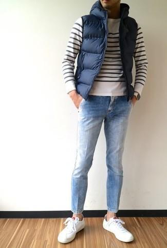Cómo combinar: chaleco de abrigo acolchado azul marino, jersey con cuello circular de rayas horizontales en blanco y negro, vaqueros celestes, tenis de cuero blancos