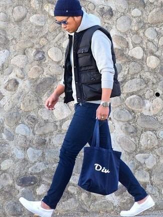 Cómo combinar: chaleco de abrigo acolchado negro, sudadera con capucha gris, vaqueros pitillo azul marino, zapatillas slip-on de lona blancas