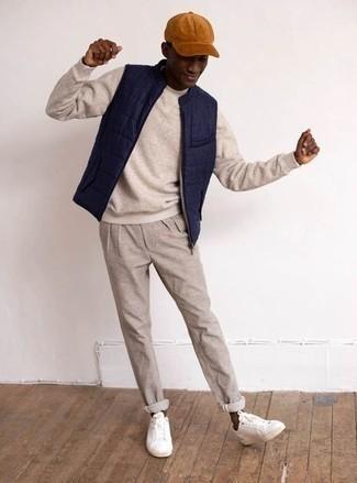 Cómo combinar un chaleco de abrigo acolchado azul marino: Haz de un chaleco de abrigo acolchado azul marino y un pantalón chino en beige tu atuendo para una vestimenta cómoda que queda muy bien junta. Tenis de lona blancos son una opción inmejorable para complementar tu atuendo.