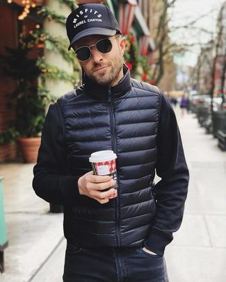 Cómo combinar: chaleco de abrigo negro, sudadera negra, vaqueros negros, gorra de béisbol estampada en negro y blanco