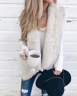 Cómo combinar: chaleco de piel de oveja en beige, camiseta de manga larga blanca, vaqueros pitillo desgastados azules, sombrero de lana negro