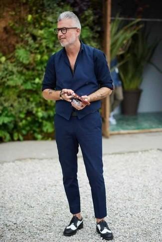 Cómo combinar: chaleco de vestir azul marino, camisa de vestir azul marino, pantalón chino azul marino, zapatos brogue de cuero en negro y blanco