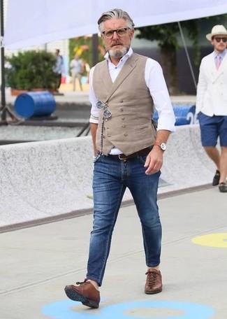 Cómo combinar: chaleco de vestir en beige, camisa de vestir blanca, vaqueros pitillo azules, tenis de cuero marrónes