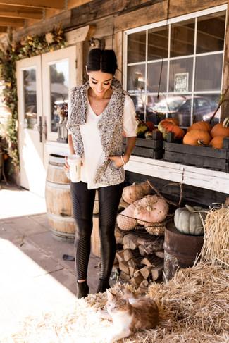 Cómo combinar: chaleco de pelo gris, jersey de manga corta blanco, pantalones pitillo de cuero negros, botines de cuero negros
