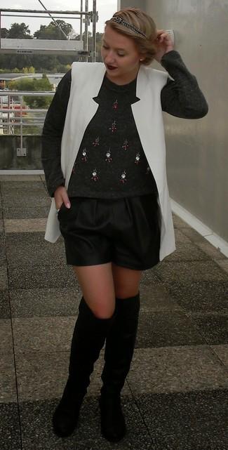 Cómo combinar: chaleco blanco, jersey con cuello circular con adornos en gris oscuro, pantalones cortos de cuero negros, botas sobre la rodilla de cuero negras