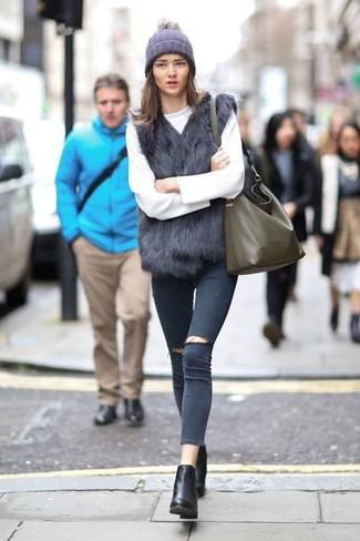 Cómo combinar: chaleco de pelo negro, jersey con cuello circular blanco, vaqueros pitillo desgastados en gris oscuro, botines de cuero negros