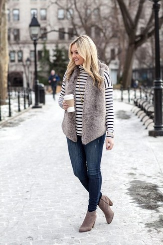 Outfits mujeres: Para crear una apariencia para un almuerzo con amigos en el fin de semana utiliza un chaleco de pelo gris y unos vaqueros pitillo azul marino. Complementa tu atuendo con botines de ante grises.