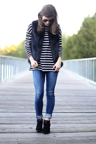 Outfits mujeres: Ponte un chaleco de pelo negro y unos vaqueros pitillo azules para conseguir una apariencia relajada pero chic. Elige un par de botines con cordones de ante negros para mostrar tu lado fashionista.