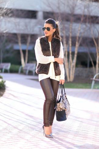 Cómo combinar: chaleco de pelo negro, jersey oversized de punto blanco, leggings de cuero negros, zapatos de tacón de cuero plateados