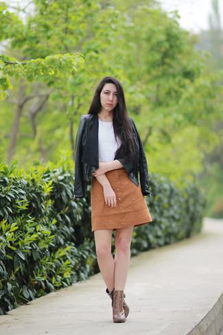Empareja una chaqueta de cuero сon flecos negra con una falda con botones marrón claro para lidiar sin esfuerzo con lo que sea que te traiga el día. ¿Por qué no ponerse botines de cuero de serpiente marrónes a la combinación para dar una sensación más clásica?