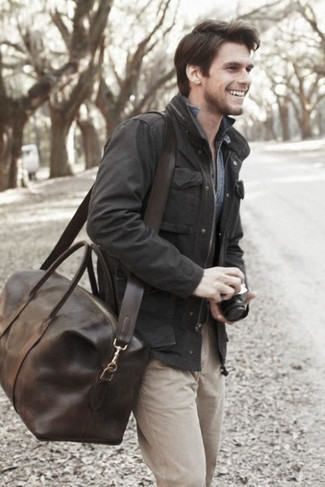 Cómo combinar: chaqueta campo negra, camisa vaquera azul, pantalón chino en beige, bolsa de viaje de cuero en marrón oscuro