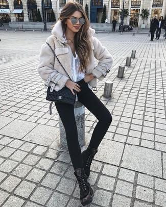 Cómo combinar: chaqueta de piel en beige, blusa de botones de gasa blanca, vaqueros pitillo negros, botas planas con cordones de ante negras