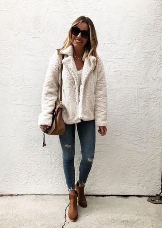 Cómo combinar: chaqueta de piel blanca, camiseta con cuello circular blanca, vaqueros pitillo desgastados azul marino, botines de ante marrónes