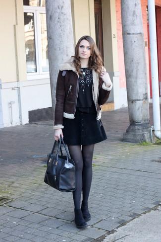 Cómo combinar: chaqueta de piel de oveja en marrón oscuro, camiseta con cuello circular bordada negra, falda con botones negra, botines chelsea de ante negros