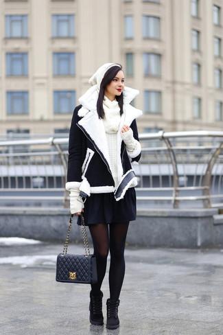 Cómo combinar: chaqueta de piel de oveja en negro y blanco, jersey con cuello circular blanco, falda skater negra, botas planas con cordones de ante negras