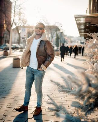 Cómo combinar: chaqueta de piel de oveja marrón, jersey con cuello circular blanco, vaqueros pitillo celestes, botas casual de cuero marrónes