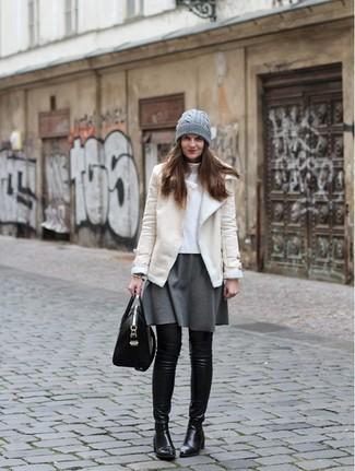 Cómo combinar: chaqueta de piel de oveja en beige, jersey de cuello alto blanco, falda skater gris, botas sobre la rodilla de cuero negras