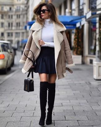 Cómo combinar: chaqueta de piel de oveja en beige, jersey de cuello alto blanco, falda skater azul marino, botas sobre la rodilla de ante negras