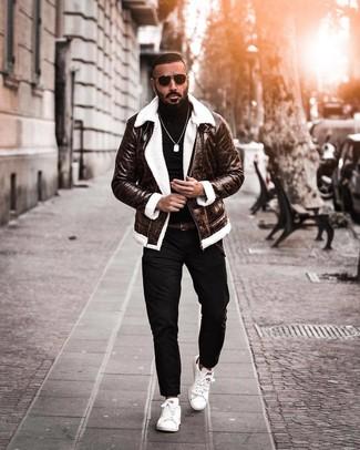 Cómo combinar: chaqueta de piel de oveja en marrón oscuro, jersey de cuello alto negro, pantalón chino negro, tenis de cuero blancos