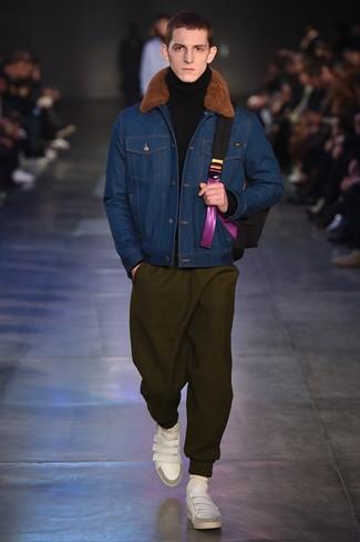 Cómo combinar: chaqueta de piel de oveja vaquera azul, jersey de cuello alto de lana negro, pantalón de chándal verde oliva, tenis de cuero blancos