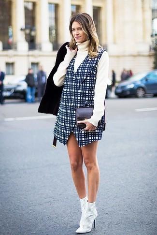 Cómo combinar: chaqueta de piel de oveja negra, jersey de cuello alto en beige, pichi a cuadros azul marino, botines de cuero con recorte blancos