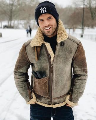 Look de moda: Chaqueta de piel de oveja marrón, Jersey de cuello alto negro, Vaqueros azul marino, Gorro estampado en negro y blanco