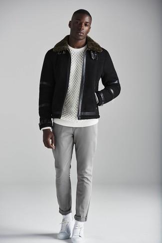 Cómo combinar: chaqueta de piel de oveja negra, jersey de ochos blanco, pantalón chino gris, tenis de cuero blancos