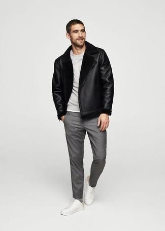 Cómo combinar: chaqueta de piel de oveja negra, sudadera gris, pantalón de vestir gris, tenis de cuero blancos