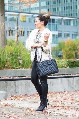 Cómo combinar: chaqueta de piel blanca, pantalones pitillo de cuero negros, botines con cordones de cuero negros, bolsa tote de cuero acolchada negra