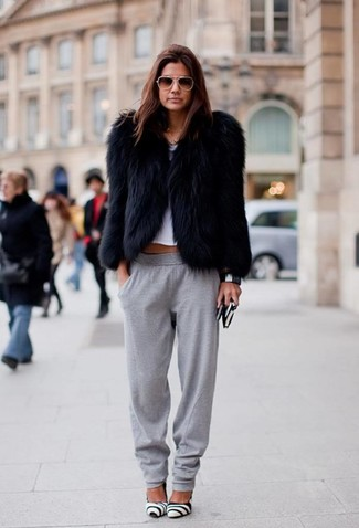 Cómo combinar: chaqueta de piel negra, top corto blanco, pantalón de chándal gris, zapatos de tacón de cuero en blanco y negro