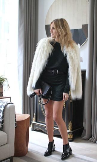 Cómo combinar: chaqueta de piel en beige, vestido jersey negro, botines chelsea de cuero negros, bolso bandolera de cuero negro