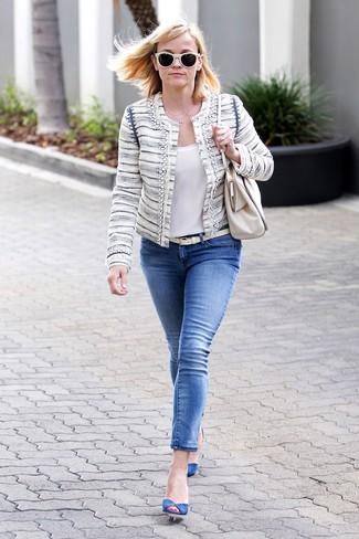 Cómo combinar: chaqueta de tweed en beige, blusa sin mangas de seda blanca, vaqueros pitillo azules, zapatos de tacón de ante azules