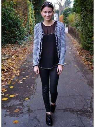 Cómo combinar: chaqueta de tweed gris, blusa sin mangas de seda negra, vaqueros pitillo de cuero negros, zapatos oxford de cuero negros