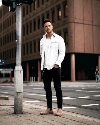 Cómo combinar: chaqueta estilo camisa blanca, camiseta con cuello circular blanca, vaqueros negros, botines chelsea de ante marrónes
