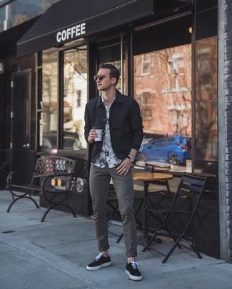 Cómo combinar: chaqueta estilo camisa negra, camisa de manga corta con print de flores en blanco y negro, pantalón chino en gris oscuro, tenis de lona negros