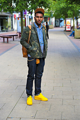 Cómo combinar: chaqueta estilo camisa de camuflaje verde oliva, camisa de manga larga azul, vaqueros azul marino, tenis de cuero amarillos