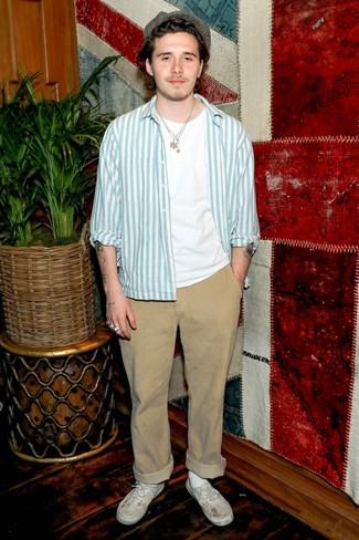 Cómo combinar: chaqueta estilo camisa de rayas verticales celeste, camiseta con cuello circular blanca, pantalón chino marrón claro, tenis de lona blancos