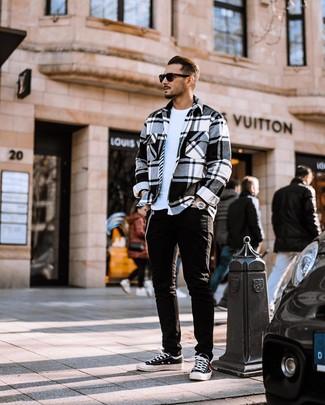Cómo combinar: chaqueta estilo camisa de franela de tartán en blanco y negro, camiseta con cuello circular blanca, vaqueros negros, tenis de lona en negro y blanco
