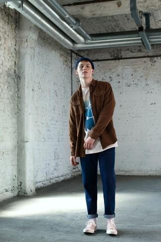 Cómo combinar: chaqueta estilo camisa marrón, camiseta con cuello circular estampada en blanco y azul, vaqueros azules, tenis de lona blancos