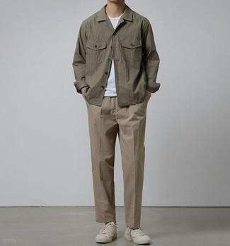 Cómo combinar una camiseta: Para un atuendo que esté lleno de caracter y personalidad usa una camiseta y un pantalón chino marrón. Con el calzado, sé más clásico y completa tu atuendo con tenis de lona blancos.
