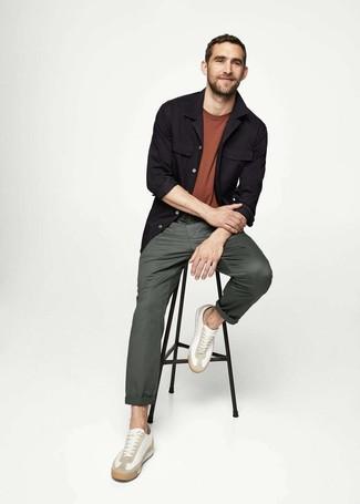 Cómo combinar: chaqueta estilo camisa negra, camiseta con cuello circular marrón, pantalón chino verde oscuro, tenis de cuero blancos