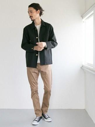 Cómo combinar unos tenis de lona en negro y blanco: Opta por una chaqueta estilo camisa negra y un pantalón chino marrón claro para crear un estilo informal elegante. Tenis de lona en negro y blanco añaden un toque de personalidad al look.