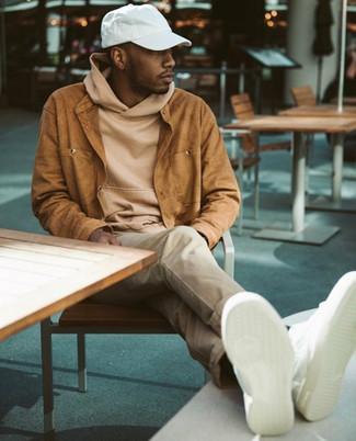 Cómo combinar: chaqueta estilo camisa de ante en tabaco, sudadera con capucha marrón claro, pantalón chino en beige, tenis de cuero blancos