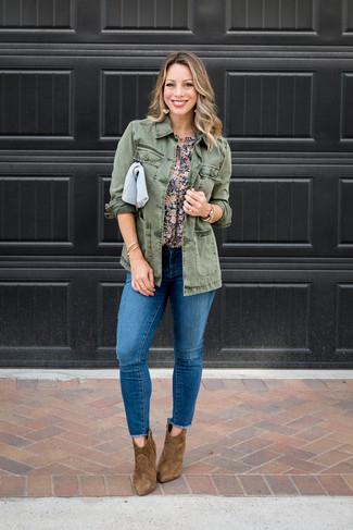 Cómo combinar: chaqueta militar verde oliva, blusa de manga corta con print de flores azul marino, vaqueros pitillo desgastados azules, botines de ante marrónes