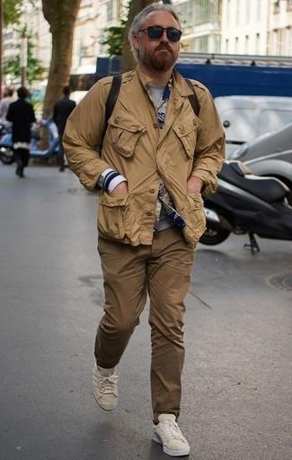 Cómo combinar un pantalón chino marrón: Empareja una chaqueta militar marrón claro con un pantalón chino marrón para lidiar sin esfuerzo con lo que sea que te traiga el día. Si no quieres vestir totalmente formal, opta por un par de tenis de lona en beige.