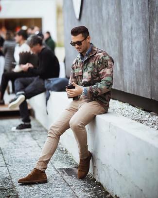 Cómo combinar: chaqueta militar de camuflaje verde oliva, camisa vaquera azul, vaqueros pitillo en beige, botas formales de ante marrónes
