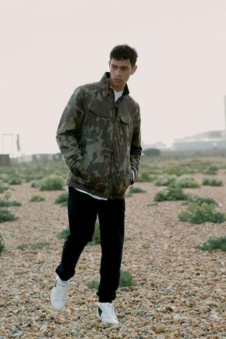 Elige una chaqueta militar de camuflaje verde oliva y un pantalón de chándal negro de Givenchy para conseguir una apariencia relajada pero elegante. Este atuendo se complementa perfectamente con tenis de cuero blancos.