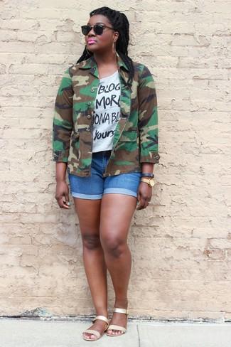Cómo combinar: chaqueta militar de camuflaje verde oliva, camiseta con cuello circular estampada en blanco y negro, pantalones cortos vaqueros azules, sandalias planas de cuero doradas