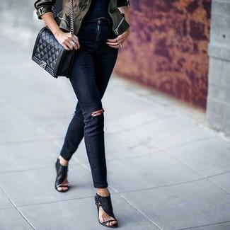 Cómo combinar: chaqueta militar de camuflaje verde oliva, vaqueros pitillo desgastados negros, sandalias de tacón de cuero negras, bolso bandolera de cuero acolchado negro