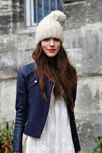 Cómo combinar: chaqueta motera de cuero azul marino, cárdigan en beige, vestido recto de encaje blanco, gorro en beige